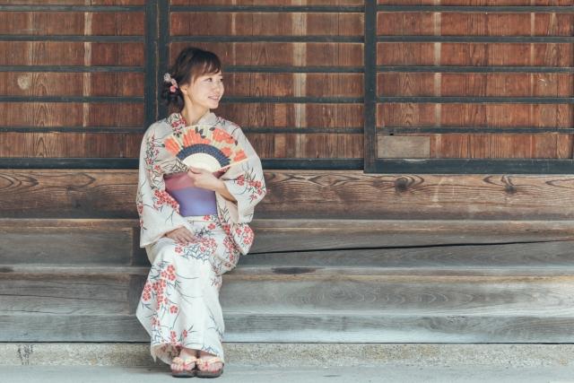 軒先で座る浴衣の女性